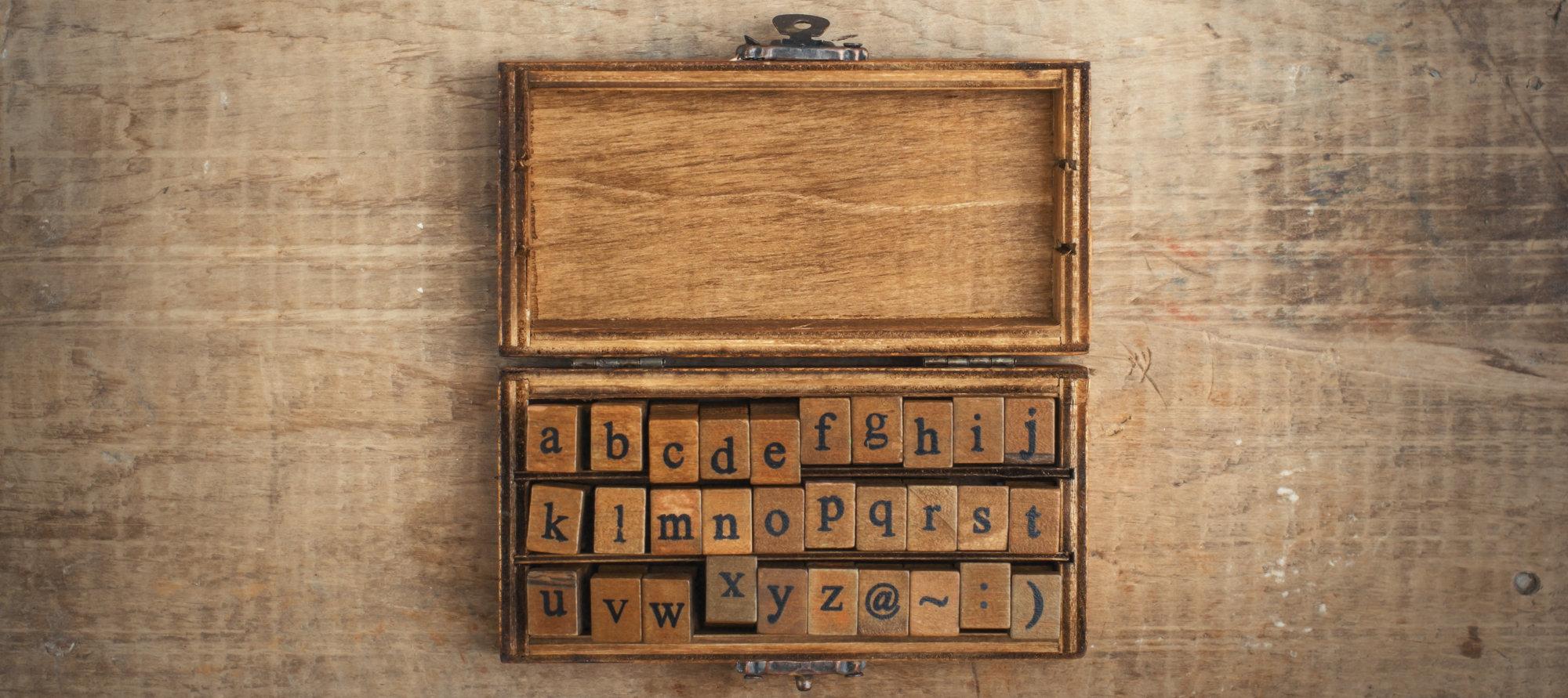 wooden stamps alphabet in old vintage box on grunge background
